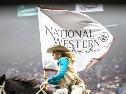Cavalgando com a faixa do Festival nacional rural e rodeio de Denver