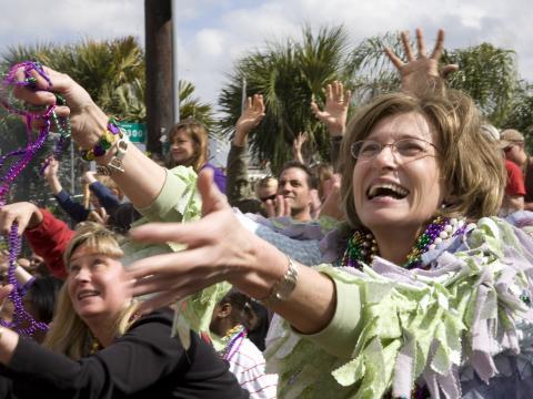 Foliões pegando colares de miçangas no desfile de Mardi Gras, em Lafayette