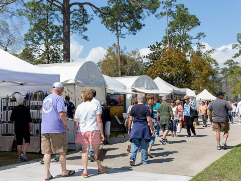 Patrons browsing artists' tents at the Orange Beach Festival of Art in Alabama