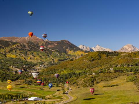 Balões de ar quente sobrevoando a paisagem durante o Snowmass Balloon Festival, no Colorado
